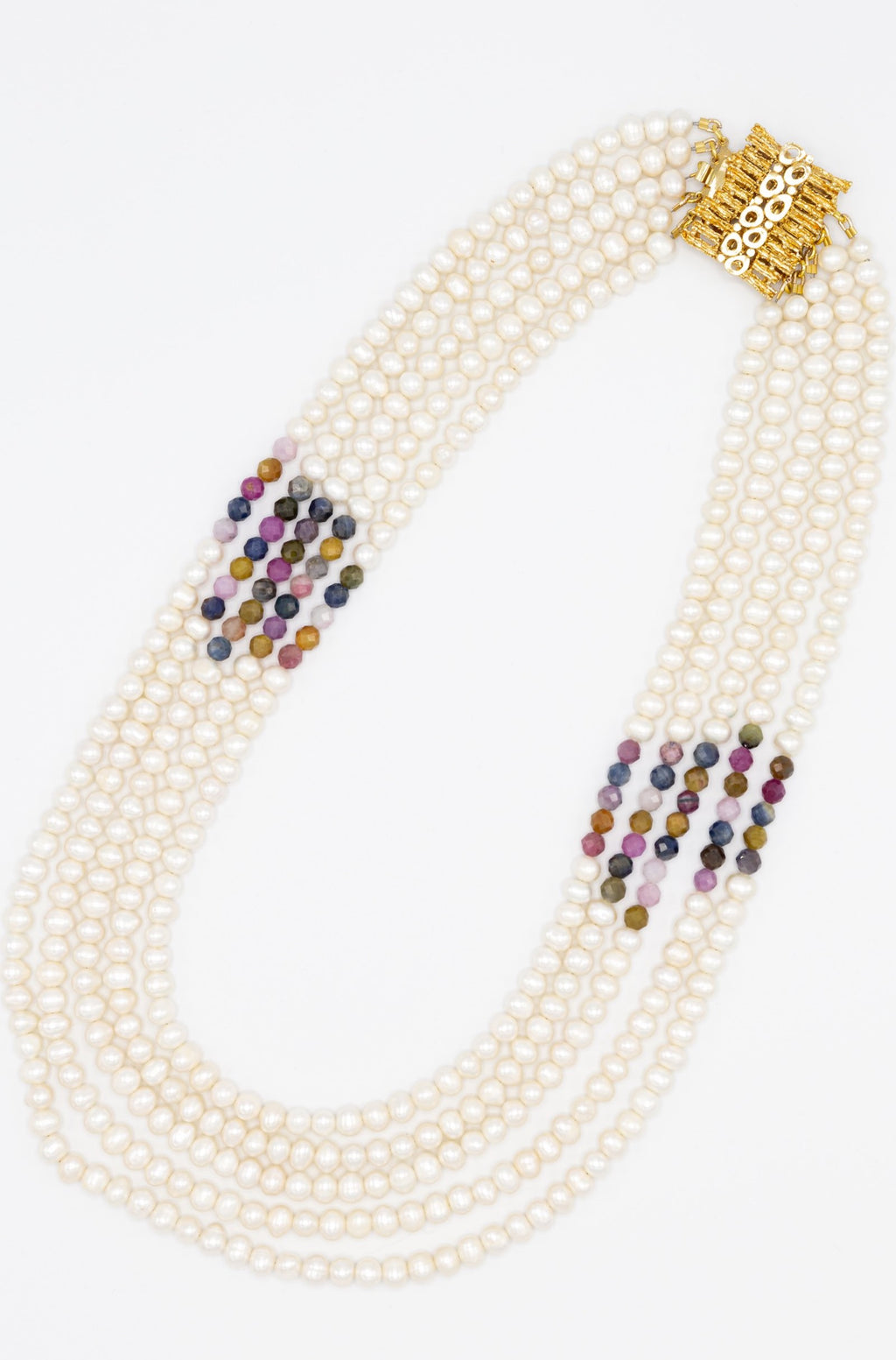 Inspired by traditional carpentry, this outstanding necklace features five rows of carefully curated freshwater pearls and multicolour rubies. Finished with eye- catching gold plated silver clasp