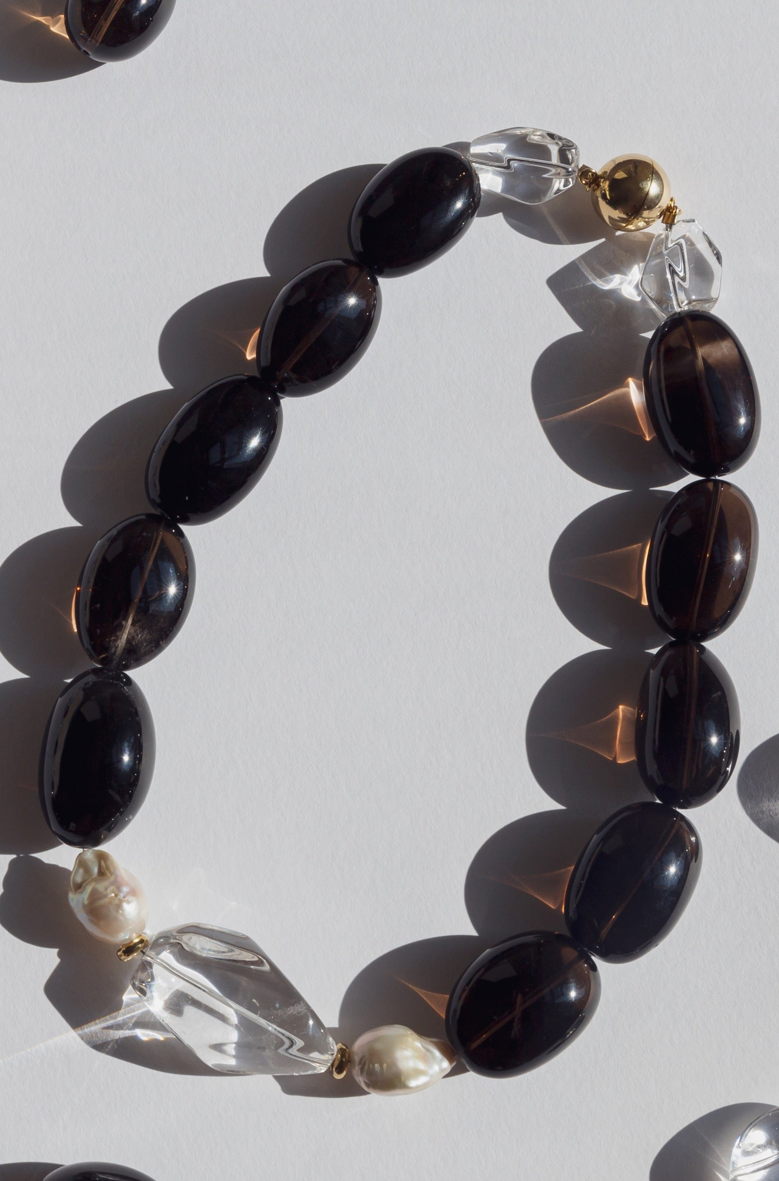 Always elegant and exquisite dark smokey quartz and white colour combination adds to every style. Smokey and crystal clear quartz, accompanied with baroque pearls, gold plated silver round beads and magnetic clasp