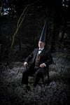 surreal man in conemen sitting on a chair wearing a suit in a forest at night