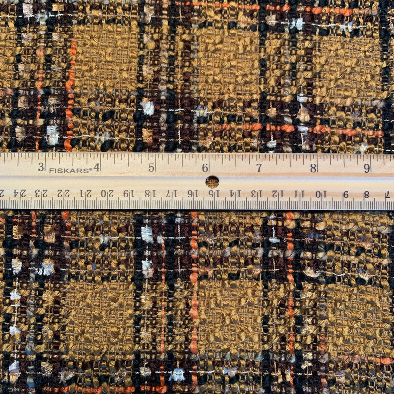 Italian Tweed plaid in golden brown, cream, black and with and orange stripe with a ruler measuring the plaid