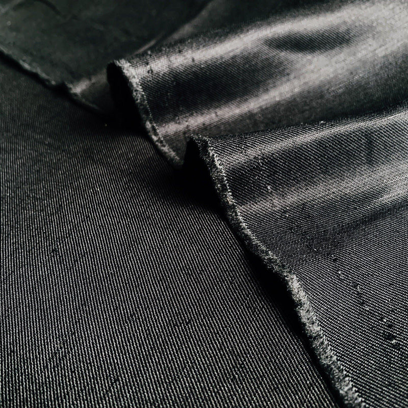 Black Sateen silk wool twill fabric with a light hitting the side to show texture and drape