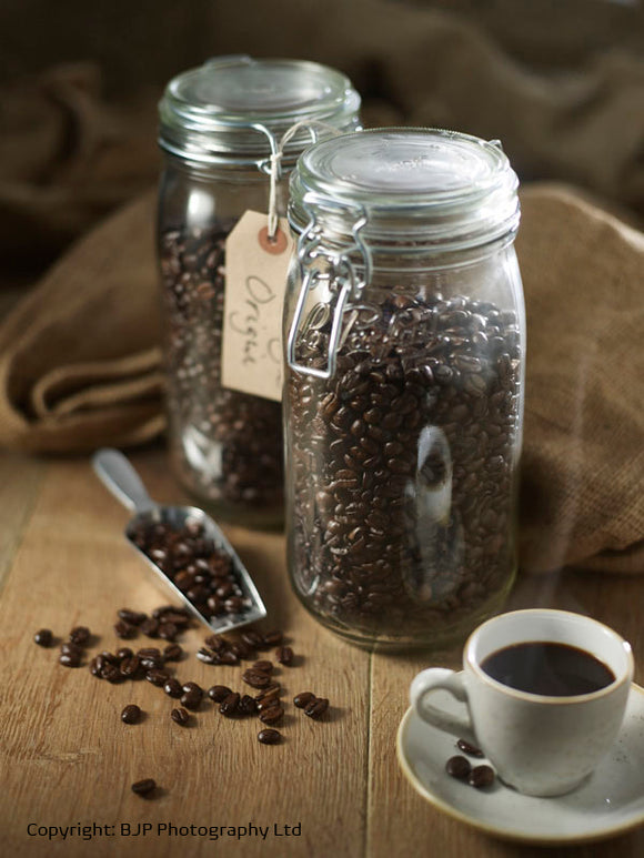 #HEXLife coffee beans in a jar and a cup of coffee on a wooden bench with hessian background.