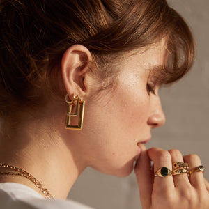 Side profile, model -brown hair up in bun, wearing Pawnshop Gold Plated Sterling Silver Large & Small Rectangle Hoop Earrings, Two tone hoop earrings. Models hand to mouth, wearing a select of Vintage Pawnshop 9K Gold Rings.