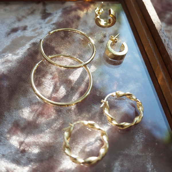 close up shot of 3 pairs of gold hoop earrings- classic 9k gold, twist 9k gold and chunky gold plated hoop earrings. Hoops are on pink crushed velvet background.
