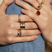 Load image into Gallery viewer, Close up models hands on denim knee, wearing an assortment of Pawnshop Signature & Vintage Rings- Vintage 9K Gold Trellis Ring is on her wedding finger.