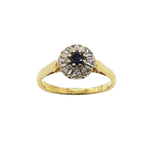 Vintage 18K gold ring- smooth band, sapphire centre and diamond surround flower. Hallmarks inner band. White background.
