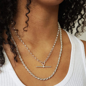 Close up Model's neck wearing two necklaces- Vintage  Sterling Silver T-Bar & Rope Chain Necklaces. Mosel is wearing white ribbed vest & black curly hair is down.