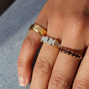 Close up models hand on lap, wearing blue jeans. Model is wearing Vintage 9K Gold Garnet Half Eternity Ring on her middle finger, Vintage Diamante MUM ring on her wedding finger, and Pawnshop Gold Plated Sterling Silver Classic Pinky Ring on her little finger.