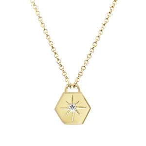 Close up product shot of pawnshop gold plated sterling silver hexagon pendant with starburst necklace. Clear  crystal rhinestone is in the centre of the pendant with engraved starburst surround. Product is shot on a white background.