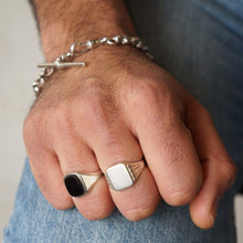 Load image into Gallery viewer, Close up models hand and arm wresting on lap, wearing blue jeans. T Bar Silver Bracelet on wrist, and signet rings in silver, black onyx on middle and wedding finger, hand clasp closed.