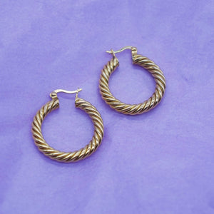 PHOTOGRAPH OF PAWNSHOP GOLD PLATED STERLING SILVER TWISTED HOOPS PLACED ON LILAC TISSUE PAPER