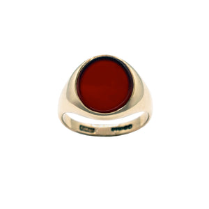 Vintage 9K gold signet ring, plain band, with Oval Red Cornelian Stone centre. Hallmarks in back of band. White background.