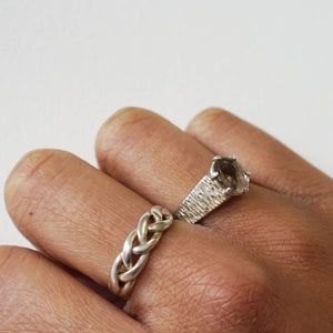 Close up models hand / knuckles wearing Vintage plaited silver ring on her middle finger & the Vintage Sterling Silver Smoky Quartz Ring with ridged band on wedding finger, background white