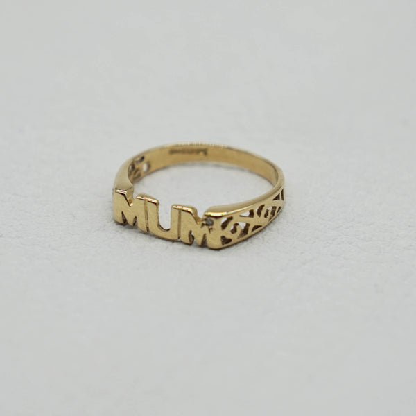 Side profile of Vintage 9K Gold Mum Ring- can see small diamond in the last M, trellis sides, hallmarks on inner band, background white.