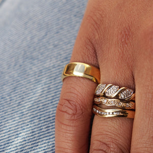 Close up Models hand on lap, wearing blue denim jeans. On her wedding finger the Vintage 9K Gold Wavy Diamond Ring is stacked with Vintage Gold Diamond Wave & Wishbone Rings, on her little finger is Pawnshop Gold Plated Sterling Silver Classic Band Pinky Ring