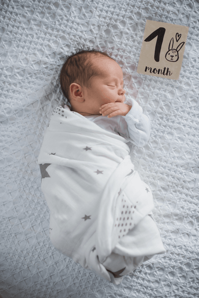 Swaddled baby boy with Scandinavian black and white milestone card printed on Kraft paper
