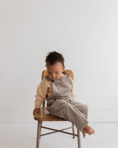 "baby sitting on wooden chair wearing ""alpy baby"" chunky oversized pullover and corduroy overalls with metal buckle accessories"