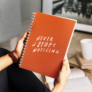Woman in her living room, holding an orange spiral journal with white hand-lettered quote about meditation on the cover.