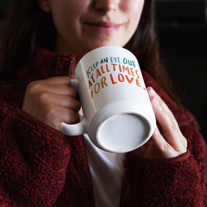Brunette female in cozy red fleece sweater holding a white coffee mug with a beautiful, colourful quote about love on it.