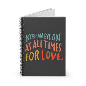 Black spiral notebook, standing up on table, showing the cover with an inspiring quote about love in colorful font.