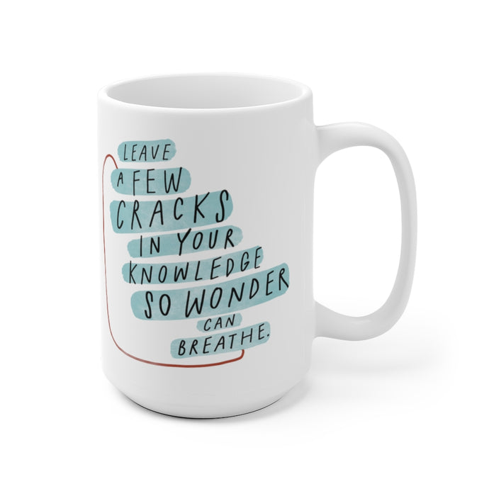 Inspiring quote about wonder and creativity printed on 15 oz white coffee mug decorated with abstract shapes.