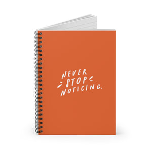 Spiral notebook, standing up on table, showing the orange cover with a big white quote about noticing the little things.