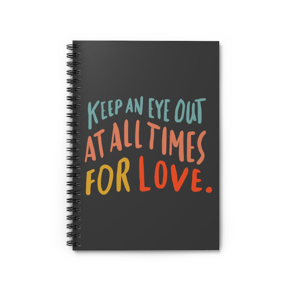 Inspiring quote about love printed in colorful big lettering on a black spiral A5 notebook.