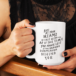 Woman's hands with black nail polish holding funky white 15 oz coffee mug with motivational quote on it in black lettering.