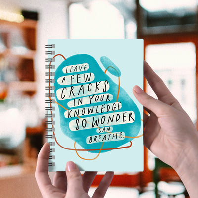 "Spiral blue 6"" x 8"" notebook with abstract shapes and a hand-lettered inspirational quote on the cover about wonder."