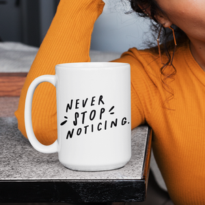 Brunette in yellow sweater lounging with white motivational statement mug with black quote about mindfulness on desk.