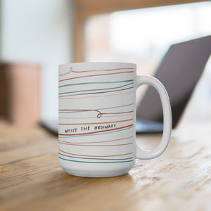 "15-ounce beautiful coffee mug on a desk. Mug is designed with whimsical colorful lines and a quote that reads ""Notice the Ordinary."""