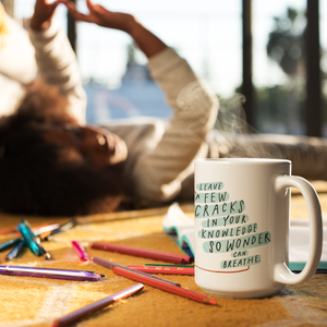 Creative scene of person laying happily on carpet behind coffee mug and colored pencils. The mug features an inspiring quote.