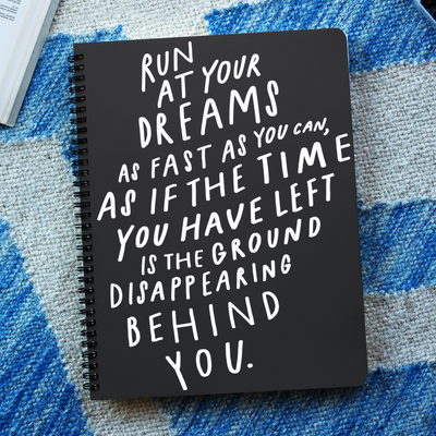 "Black and white 6"" x 8"" spiral notebook with hand-lettered and illustrated quote about following your dreams on the cover."
