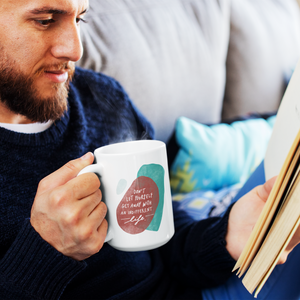 Hipster guy reading a book, holding a creative white coffee mug featuring a motivational quote and abstract shapes.