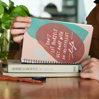 Motivating quote about living your best life hand-lettered and illustrated with abstract shapes on a spiral A5 notebook.