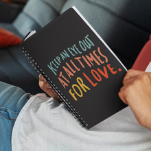 Load image into Gallery viewer, Man reclining with open spiral journal on his lap. Journal cover is black with quote about love in colourful lettering.