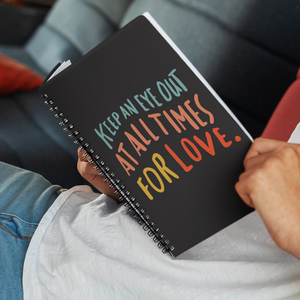 Man reclining with open spiral journal on his lap. Journal cover is black with quote about love in colourful lettering.