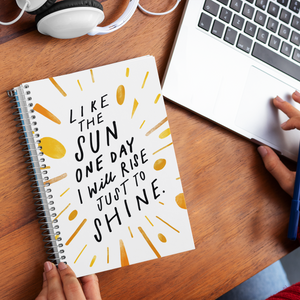 Woman hands holding a spiral journal with creatively hand-lettered quote about living your best life, on desk with laptop.