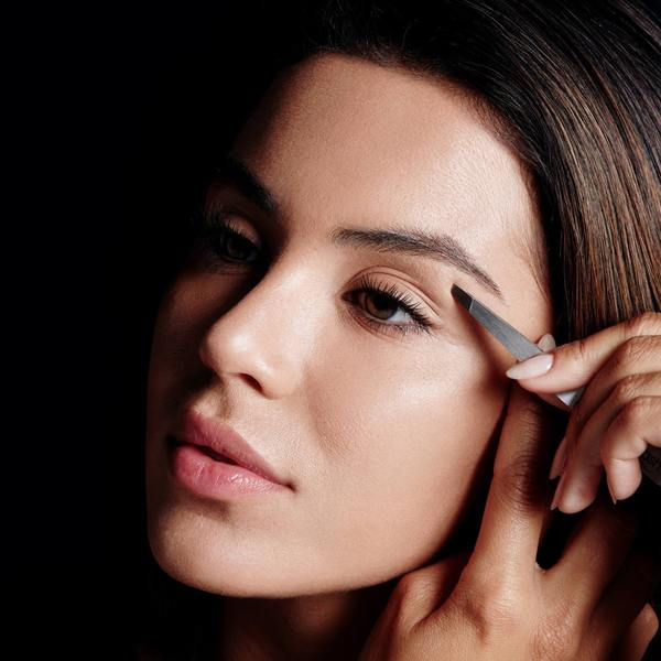 Tweeze stray hairs around the brow arch, removing only the obvious coarse/dark hair especially between the eyes.