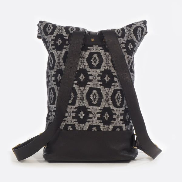Back view of black and white dhaka fabric backpack with leather