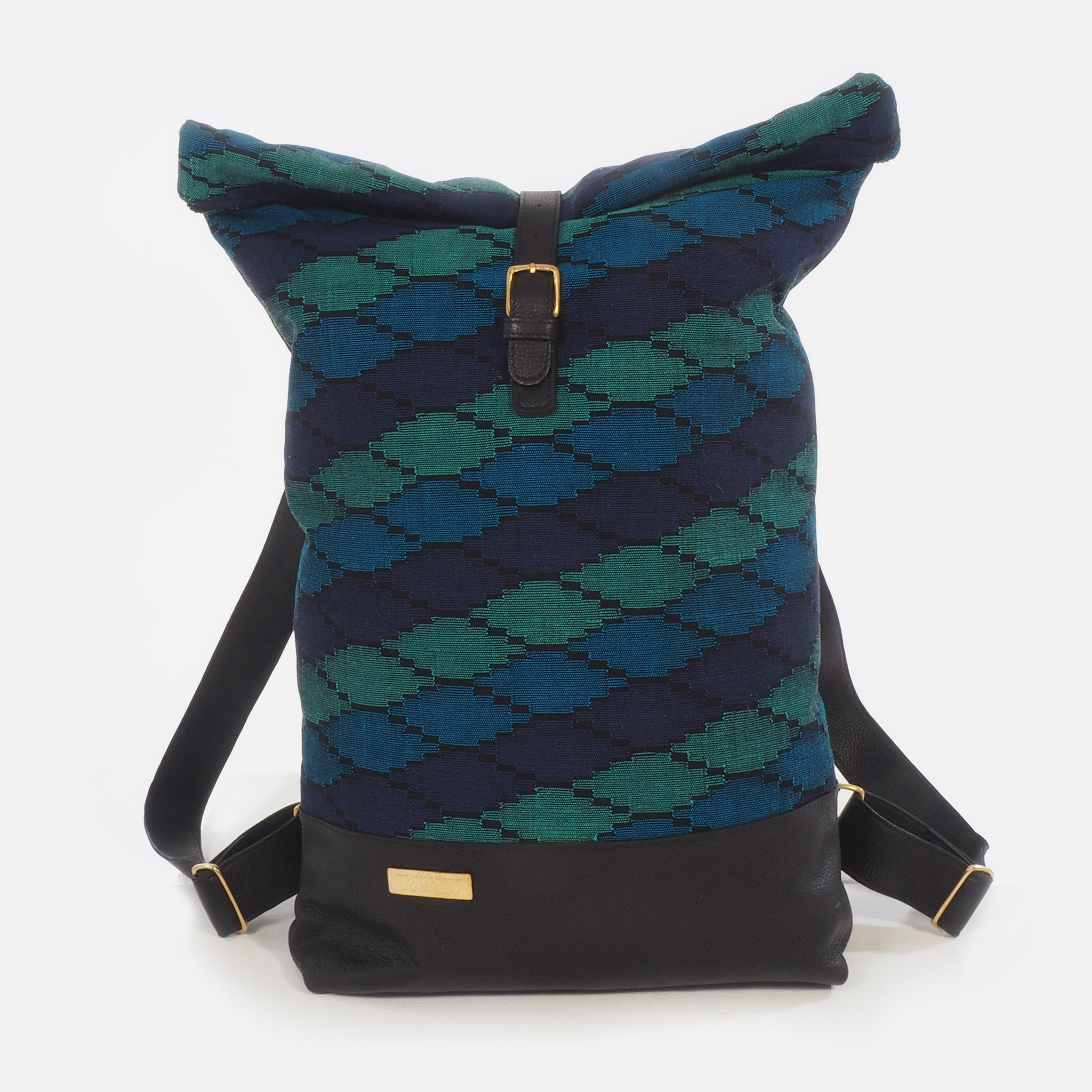 Front view of Battiayo ,Deep Blue Sea' backpack with handwoven traditional dhaka fabric from Nepal and leather. The handwoven fabric of the backpack has three different shades of blue and a bit of black. The dhaka fabric has a geometric pattern and is handwoven by amazing women. The leather is black. The straps and bottom are made from leather. The brass buckles and brass label are also made in Nepal.