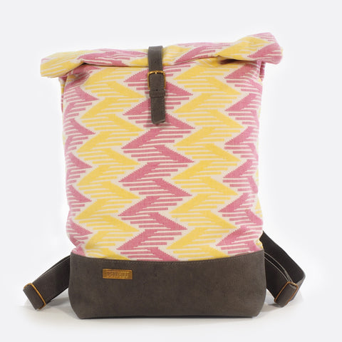 Front view of backpack with handwoven traditional dhaka fabric from Nepal and leather.  The fabric  of the backpack is mainly yellow and pink and the leather is grey . The bag has brass buckles