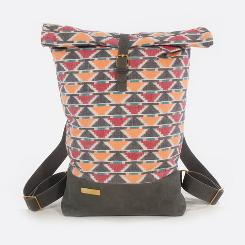 Front view of backpack with handwoven traditional dhaka fabric from Nepal and leather.  The fabric  of the backpack is mainly red, orange , green, white and black and the leather is grey . The bag has brass buckles