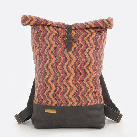 Front view of backpack with handwoven traditional dhaka fabric from Nepal and leather.  The fabric  of the backpack is mainly red, orange and black and the leather is grey . The bag has brass buckles
