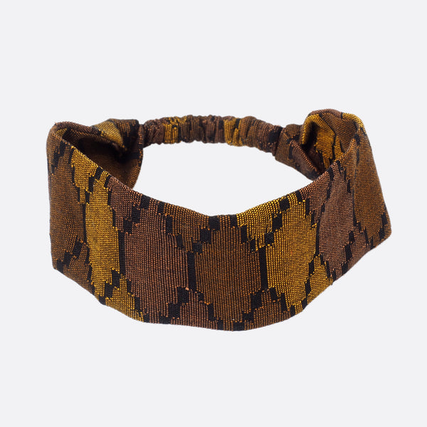 Top view of the Battiayo Deep Brown Earth headband. The handwoven traditional dhaka fabric has three different shades of brown and a bit black. The dhaka fabric has a geometric pattern and is handwoven by amazing women. The pattern looks like honeycombs.