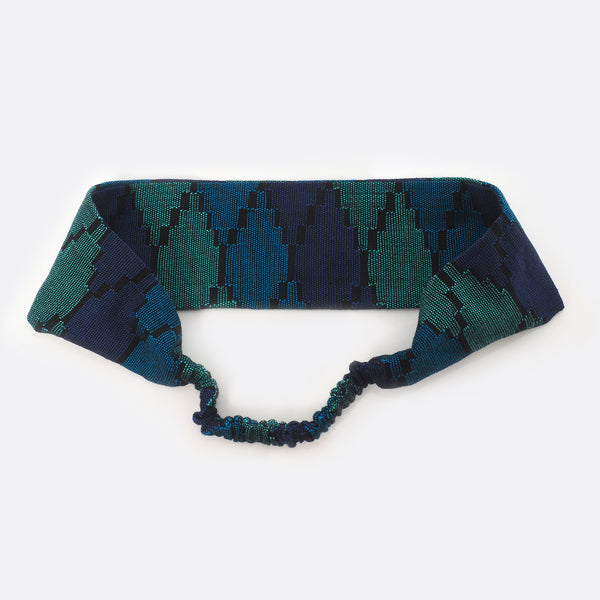 Back view of the dark blue Battiayo headband. The small scrunchy part, which gives the headband the elasticity is shown. The elastic part is covered with the dhaka fabric.