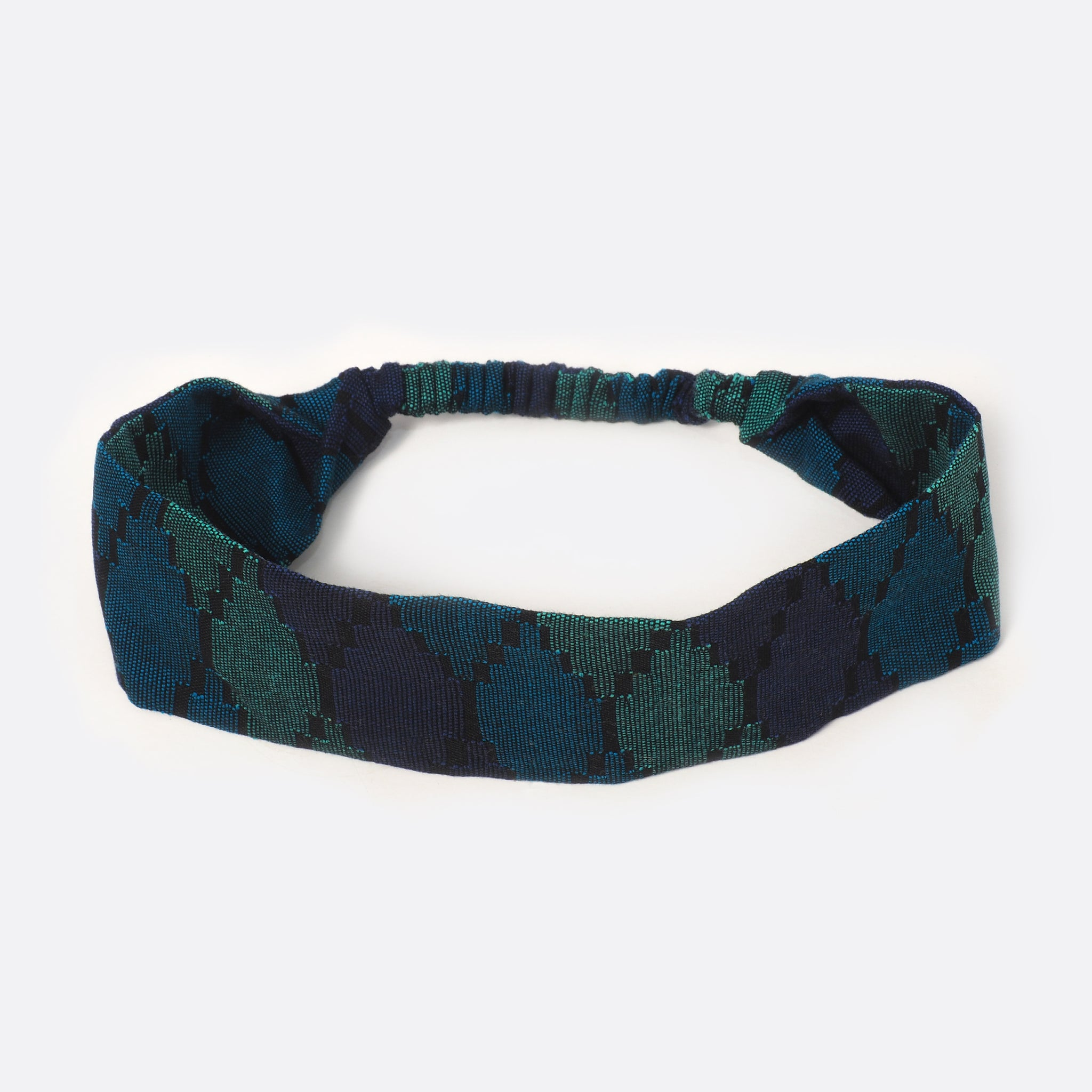 Top view of the Battiayo Deep Blue Sea headband. The handwoven traditional dhaka fabric has three different shades of blue and a bit black. The dhaka fabric has a geometric pattern and is handwoven by amazing women. The pattern looks like honeycombs.