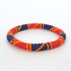 One beaded bracelet is on the picture. The bracelet is made from red, blue and orange glass beads. The bracelet has a geometric pattern. The glass beads are clearly shown. The background of the picture is white.  The Battiayo bracelets are handmade from small glass beads.
