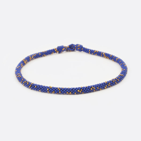 Front view of the handmade Battiayo beaded necklace. It is a single-string necklace. The necklace is mainly blue and has small golden dots.