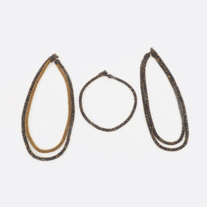 The handmade Battiayo necklace in red with golden dots is existing in three variations. All three variations are shown on the picture. On the left is the double-string necklace with both strings in red with golden dots. In the middle is the single-string necklace, which is much shorter than the double-string necklace. On the right is the double-string necklace with the longer string in red with golden dots and the shorter string completely golden.
